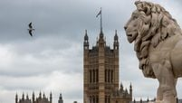 A statue of a Lion stands on Westminster Bridge in the view of the Houses of Parliament in London.