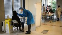 A health worker administers a swab test on a patient at a COVID-19 test center in Paris.