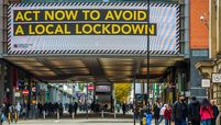 Pedestrians pass a large advertisement on the Arndale Center shopping mall reading 'Act now to avoid a local lockdown' in Manchester, England