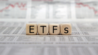 Wooden blocks spelling ETFs on a newspaper background with fever chart