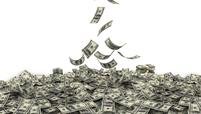 Dollar bills drifting down into a pile