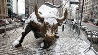 The Charging Bull statue is covered in snow near the New York Stock Exchange on Feb. 11, 2021