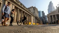Pedestrians and a cyclists pass the Bank of England in the City of London on June 24, 2020.
