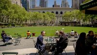 People sit outside in Bryant Park in New York