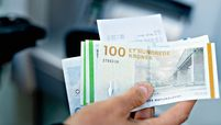 A bank customer takes Danish Kroner banknotes from an ATM in Aarhus, Denmark