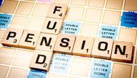Lettered wooden tiles forming the words 'pension fund' over a scrabble game cardboard