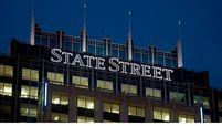 Signage for State Street Corp. is illuminated atop the State Street Financial Center building, which houses the company's headquarters, in Boston on Oct. 15, 2012