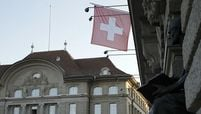 The Swiss national flag hangs from the Federal Palace, Switzerland's parliament building, in Bern, Switzerland, on Dec. 13, 2018