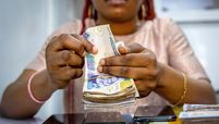 A vendor counts out Nigerian naira banknotes inside a shop at the Ikeja computer village market in Lagos, Nigeria