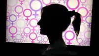 Profile of backlit woman against at TV monitor with female symbols on it
