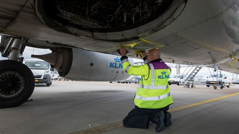 A member of the Line Maintenance Department covers an exhaust duct while carrying out essential tests on all systems on grounded KLM passenger aircraft
