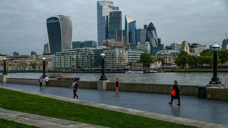 Commuters walk along the Thames Path in view of skyscrapers in London's financial district