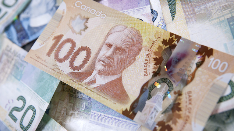 The Canadian polymer $100 bill atop a pile of the old paper bills