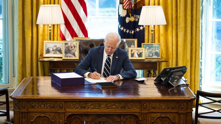 President Joe Biden signs the American Rescue Plan in the Oval Office of the White House in Washington, D.C., U.S., on Thursday, March 11, 2021. Biden signed the $1.9 trillion pandemic-relief bill into law, capping his first major legislative achievement and allowing aid to flow to tens of millions of individuals, businesses and local governments.