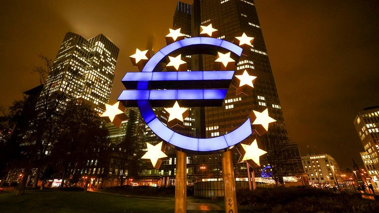 The Euro sculpture illuminated outside the Eurotower, the former headquarters of the European Central Bank in Frankfurt on Dec. 15, 2020