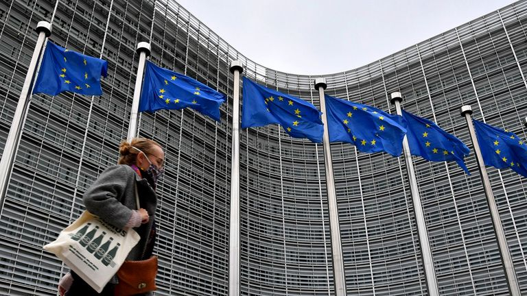 A pedestrian wears a protective face mask while passing European Union flags flying outside the Berlaymont building, headquarters of the European Commission, in Brussels