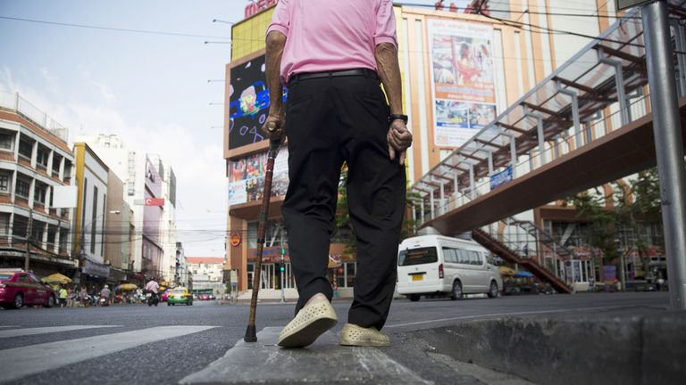 A man uses a walking cane as he walks along a road in the Chinatown area of Bangkok,