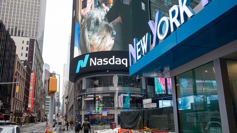 Pedestrians pass in front of the Nasdaq MarketSite in New York