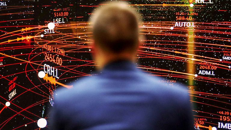 An employee views a FTSE share index board in the atrium of the London Stock Exchange Group's offices in London