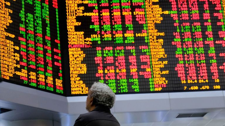 A person looks at stock prices displayed in the trading gallery of the RHB Investment Bank Bhd. headquarters in Kuala Lumpur, Malaysia