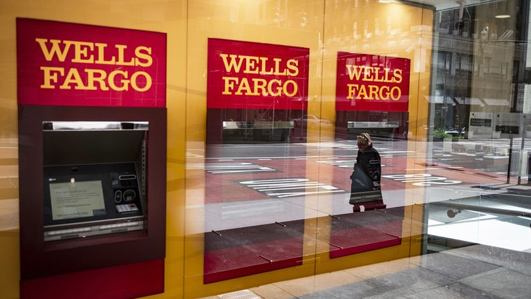 A person wearing a protective mask is reflected in the window of a temporarily closed Wells Fargo & Co. Bank branch in New York on April 10, 2020