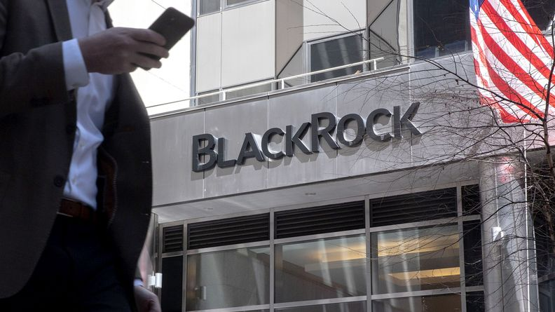 A pedestrian holding a cellphone walks past BlackRock Inc. headquarters in New York