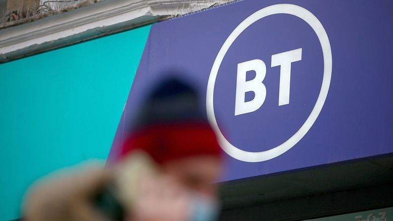 pedestrian on cellphone walking past a BT logo on a storefront