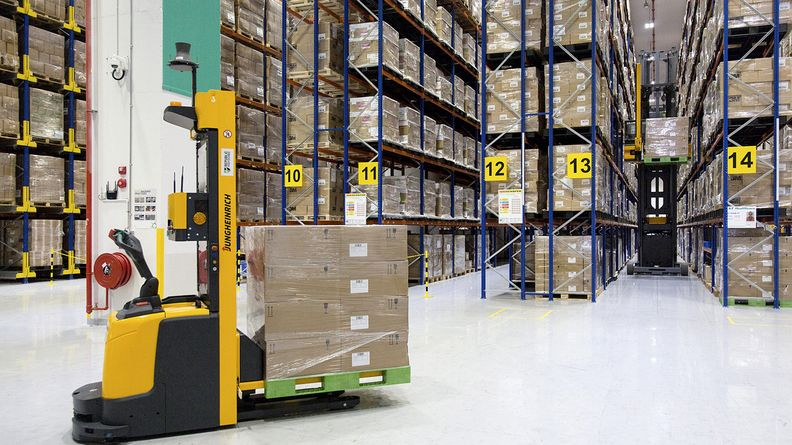 An automated guided vehicle transports boxes inside the Toll City warehousing facility in Singapore