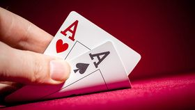 Hand revealing ace of hearts and ace of spades playing cards on a red background