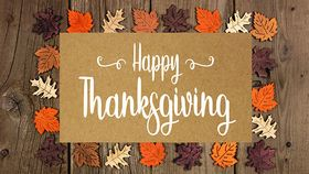 Happy Thanksgiving greeting card with frame of wooden autumn leaves over a rustic wood background