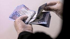 A woman counts 500 Riyal banknotes in Saudi Arabia