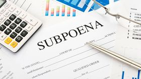 Subpoena form on a desk with paperwork
