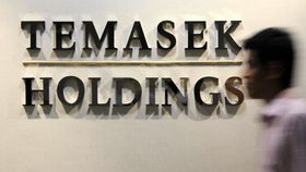 An office worker walks past a Temasek Holdings sign in the company's offices in Singapore