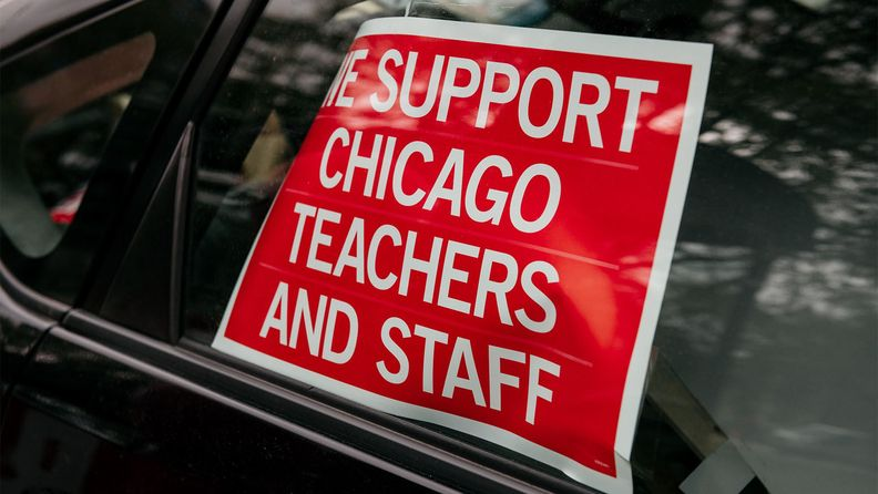 A 'We Support Chicago Teachers and Staff' sign is displayed in the window of a parked car in Chicago during the teachers' strike in 2019