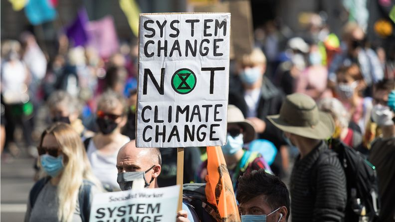An environmental campaigner holds a placard reading 'System Change, Not Climate Change' in Parliament Square during a protest by Extinction Rebellion in London