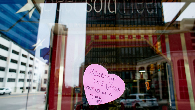 "A hand made sign placed on the window of a restaurant reads ""Beating This Virus One Heart at a Time"" in Detroit."