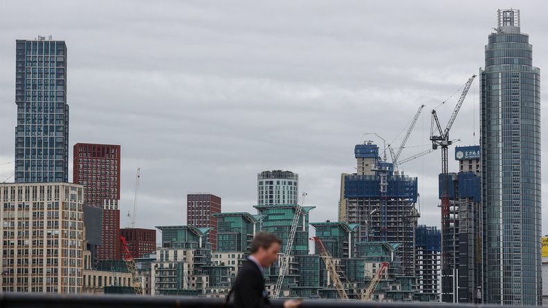 A pedestrian crosses the River Thames in view of construction work in London.