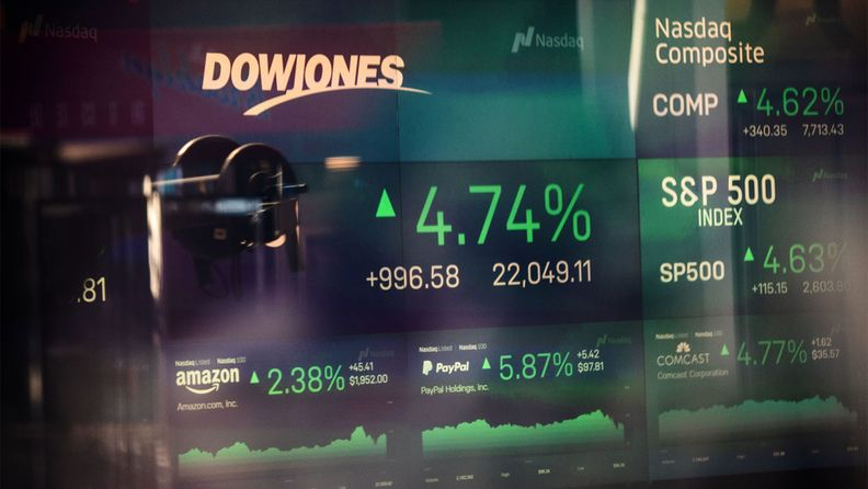 Monitors displaying stock market information are seen through the window of the Nasdaq MarketSite in Times Square on April 6, 2020