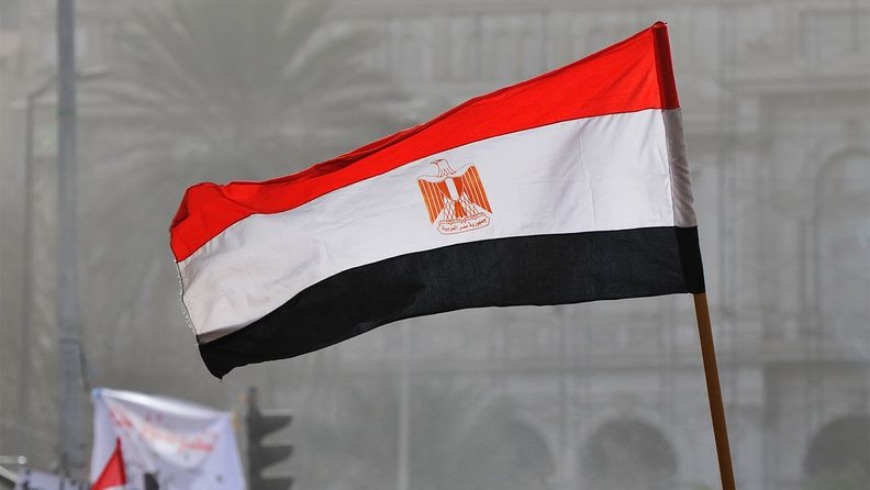 At a demonstration in Cairo's Tahrir Square, an Egyptian flag is raised above the crowd.