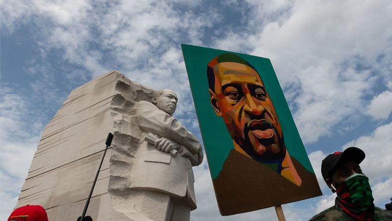 A demonstrator holds a painting of George Floyd at Martin Luther King Jr. memorial in Washington