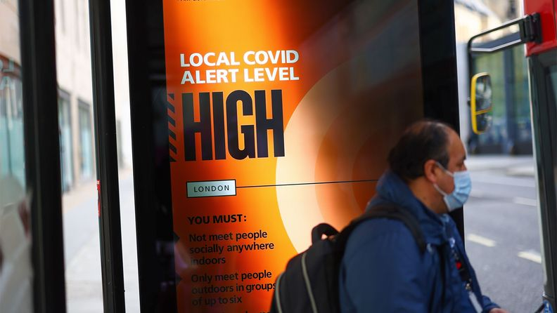 A commuter boards a bus near an advertisement showing that the Local Covid-19 Alert Level is high at a bus stop in London