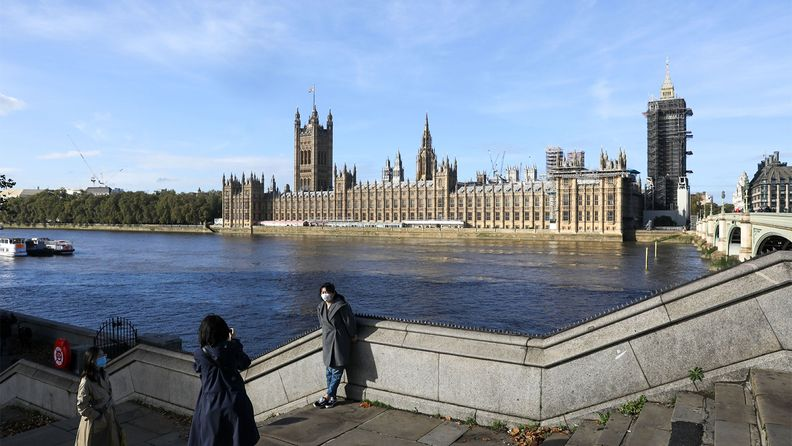 Tourists pose for photographers near the in view of the Houses of Parliament in London across the Thames River