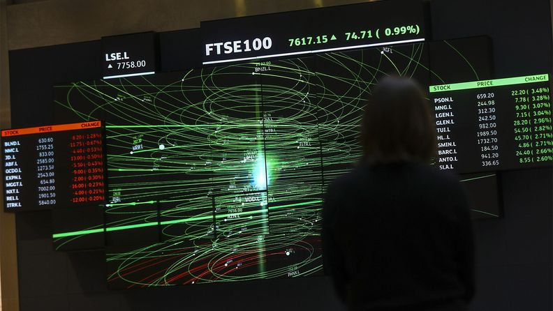 An employee views a FTSE share index board in the atrium of the London Stock Exchange Group's offices