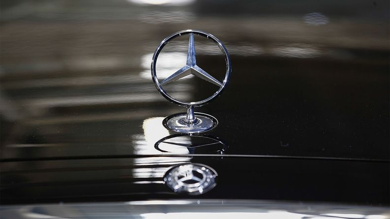 A trident hood ornament sits on the hood of a Mercedes S500 luxury sedan