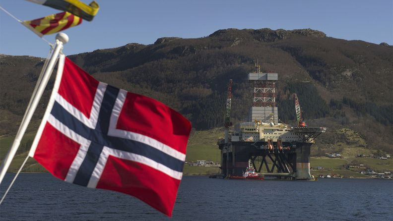 A Norwegian national flag flies from a vessel near the Scarabeo 8 deepwater oil drilling rig