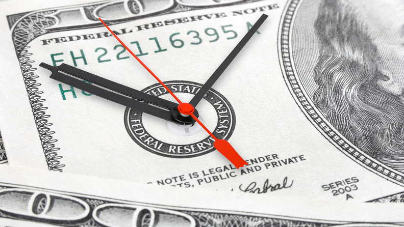 clock on the face of a $100 bill