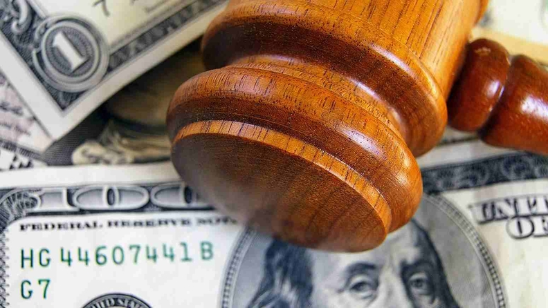 A judge's gavel laying atop $100 bills