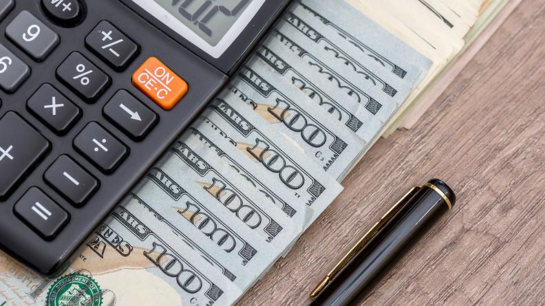 Calculators with $100 bills and pen