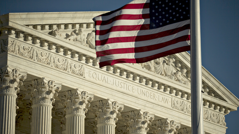 """A picture of the supreme court, with the U.S. flag waving in front of the phrase """"Equal Justice Under Law"""""""