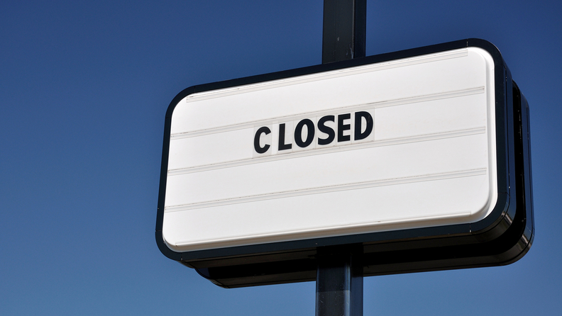 A Closed sign against a blue sky